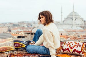 female sitting on colorful rug
