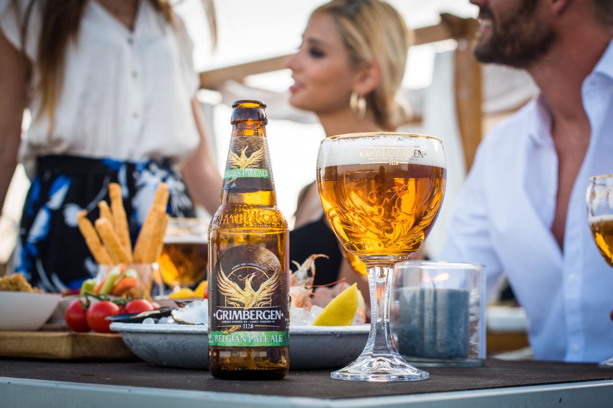 Bottle of Grimbergen Belgian Pale Ale next to full glass