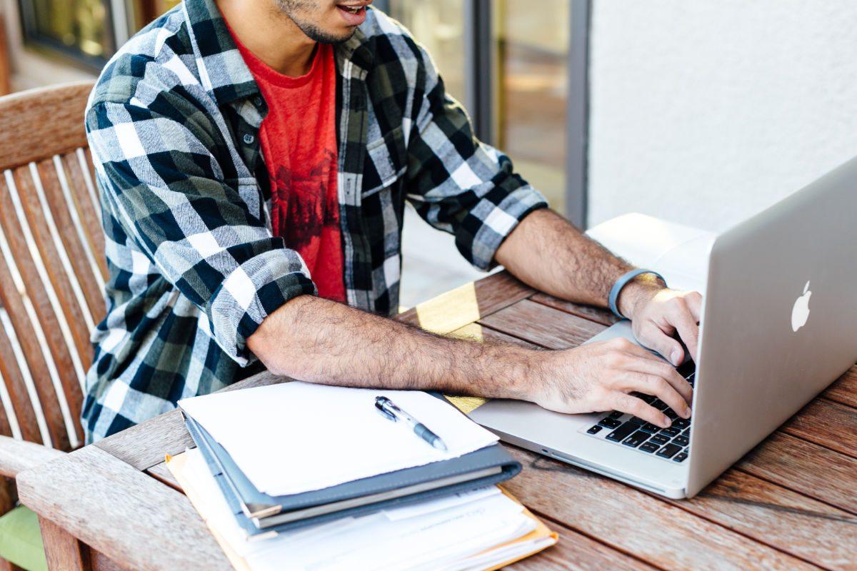 Man typing creative brief on Mac laptop